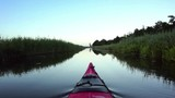 Paddling in a red kayak on a canal  in nature during sunset at the end of a beautiful summer day. Cinemagraph clip.