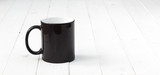 black cup with white inside on planked wooden table