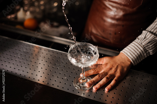 Barman pouring into champagne glass and making a splash Poster