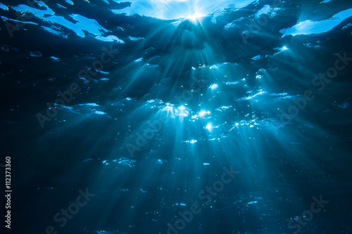 Underwater shot with sunrays in deep blue tropical sea