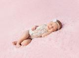 cute smiling newborn baby in wreath sleeps on blanket