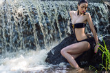 seductive woman in black swimsuit on background waterfall