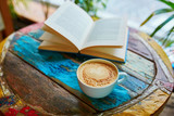 Fototapety Cup of coffee and book on a wooden table