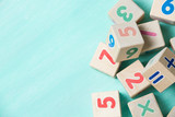Wooden cubes with numbers on a turquoise wooden background. - 112419976