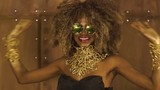 Magic surreal golden african american female model in massive sunglasses with bright glitter makeup, glossy golden hairstyle and big red lips posing and laughing on the studio background