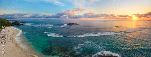Foto Murales Panoramic view of tropical beach with surfers at sunset.