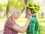 young mother dresses her son bicycle helmet