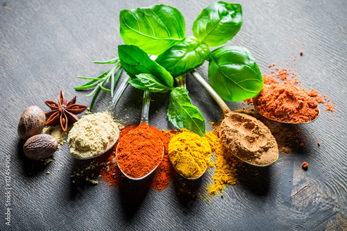 Intensive spices and herbs on old spoons
