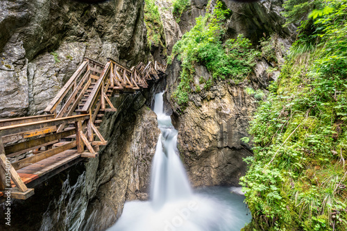Wooden boardwalk leads through a tight canyon over whitewater, Sigmund Thun Klamm, Austria