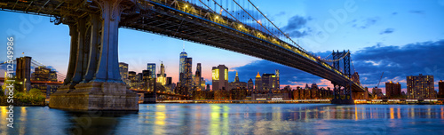 Manhattan Bridge panorama with skyline and Brooklyn Bridge at dusk, New York
