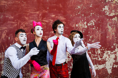 Four mimes looking aside on the background of a red wall. Poster