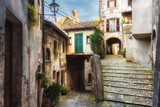 Fototapety Spring streets of the old Tuscan town. Colorful flowers bloom