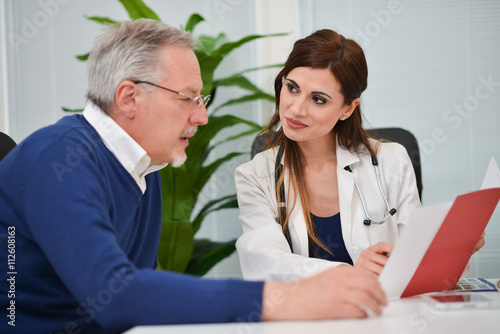 Doctor speaking to her patient while showing some documents Plakat