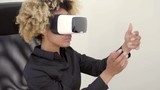 Woman wearing 3d vr goggles moving her hands in the air while exploring virtual reality.