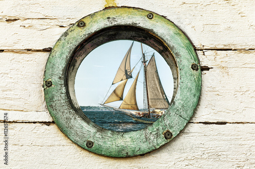 Fototapeta Old porthole window looks out at an old sailing ship. Vintage color