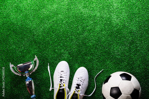 Poster Soccer ball, cleats and trophy against green artificial turf