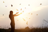 Fototapety Freedom of life, free birds and woman enjoying nature in sunset background