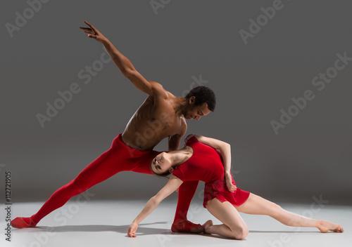 Fototapeta Couple of ballet dancers posing over gray background