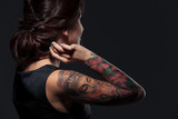 Back view of pretty young woman with tattooed hand