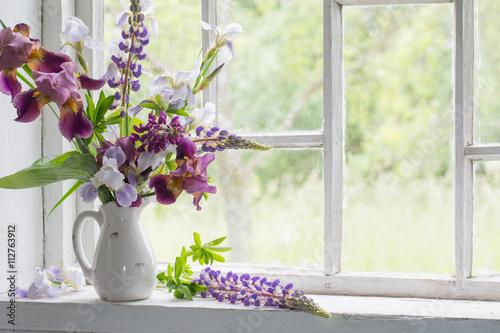 Aluminium Iris Flower vase sitting inside of window