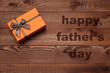 Orange box with brown ribbon on wooden background. Fathers day