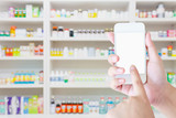 female pharmacist hold mobile smartphone in the pharmacy