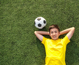 Fototapety happy teenage boy with a soccer ball lying on the green lawn