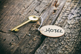 "Round wooden tag with ""Hotel"" text on a key,wooden surface"