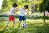 Two cute little kids, playing football together, summertime. Chi