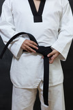 karate man tying the knot to his black belt on black background