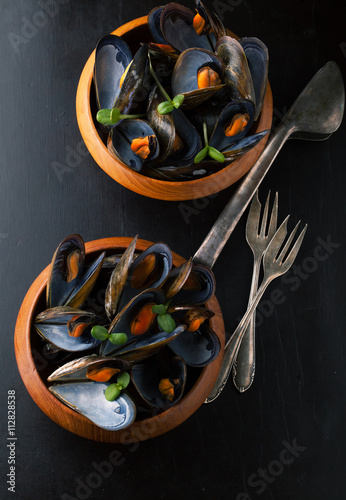 Delicious mussels with fresh herbs in a pot