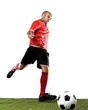 football player kicking ball in free kick shooting action isolated on white background on green grass pitch