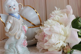 Statuette of an angel on the background with peonies and porcelain cups