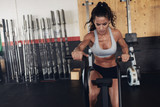Fototapety Fit young female working out on gym bike