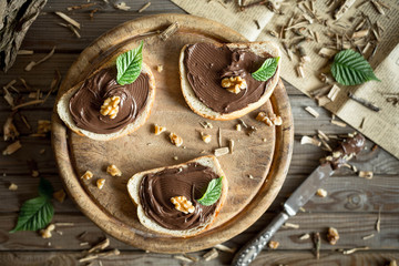 Slice of bread with chocolate cream and nuts. Chocolate spread with knife. Top view.
