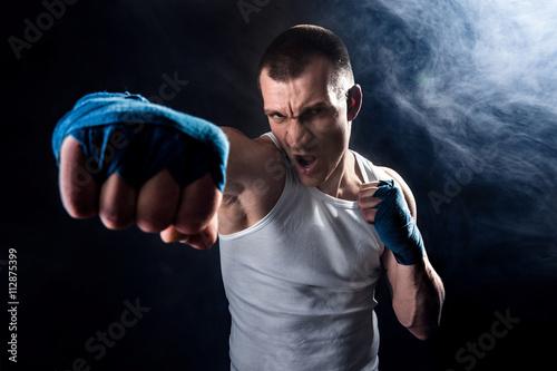 Staande foto Muscular kickbox or muay thai fighter punching in smoke.