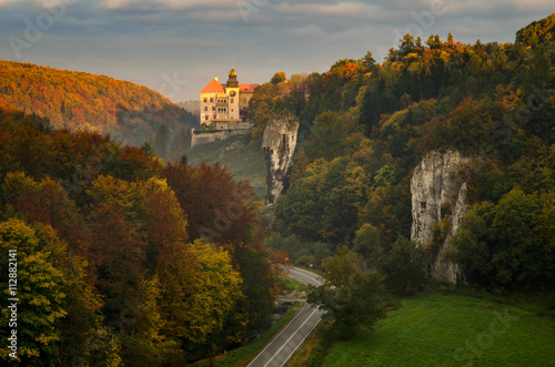 Sunrise at Pieskowa Skala Castle among autumn trees, Poland