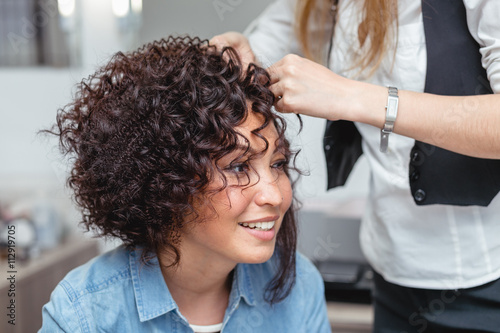 Poster A professional hairdresser makes modern fine hairdo with the curls