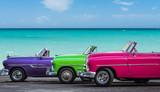 Drei amerikanische Oldtimer am Strand von Havanna Kuba