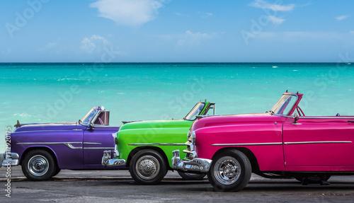Tuinposter Havana Drei amerikanische Oldtimer am Strand von Havanna Kuba