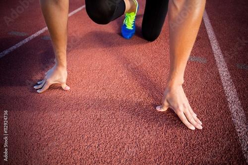 Fototapeta Female athlete in ready to run position