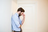 Worried man with hand on forehead leaning on wall