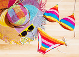 Fototapety Summer colorful bikini, straw hat and sunglasses on the wood table. Vacation fashion and shopping image.