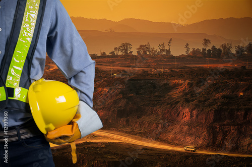 Poster Engineer holding yellow helmet with coal mining