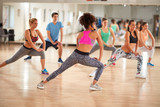 Group of fitness exercisers in colorful sports clothes in fitnes