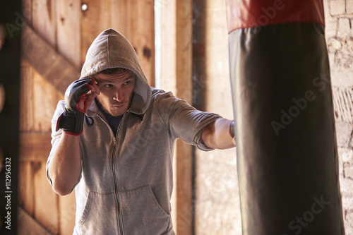 Poster Young Male Boxer Working Out With Punchbag In Gym