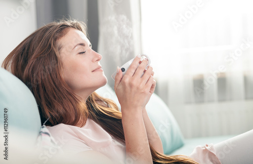 Young woman sitting on couch at home and drinking coffee. Casual style indoor shoot - 112960749