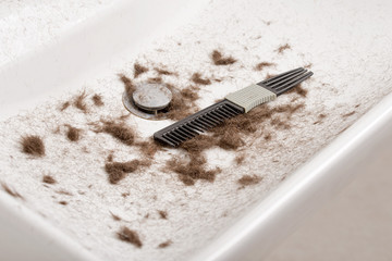 sink full of hair and dirty comb