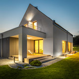 Exterior of illuminated house among green - 112982378