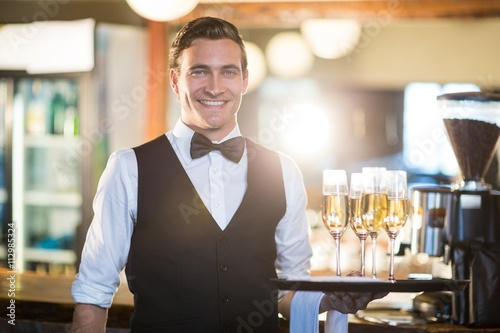 Portrait of waiter holding serving tray with champagne flutes  Poster